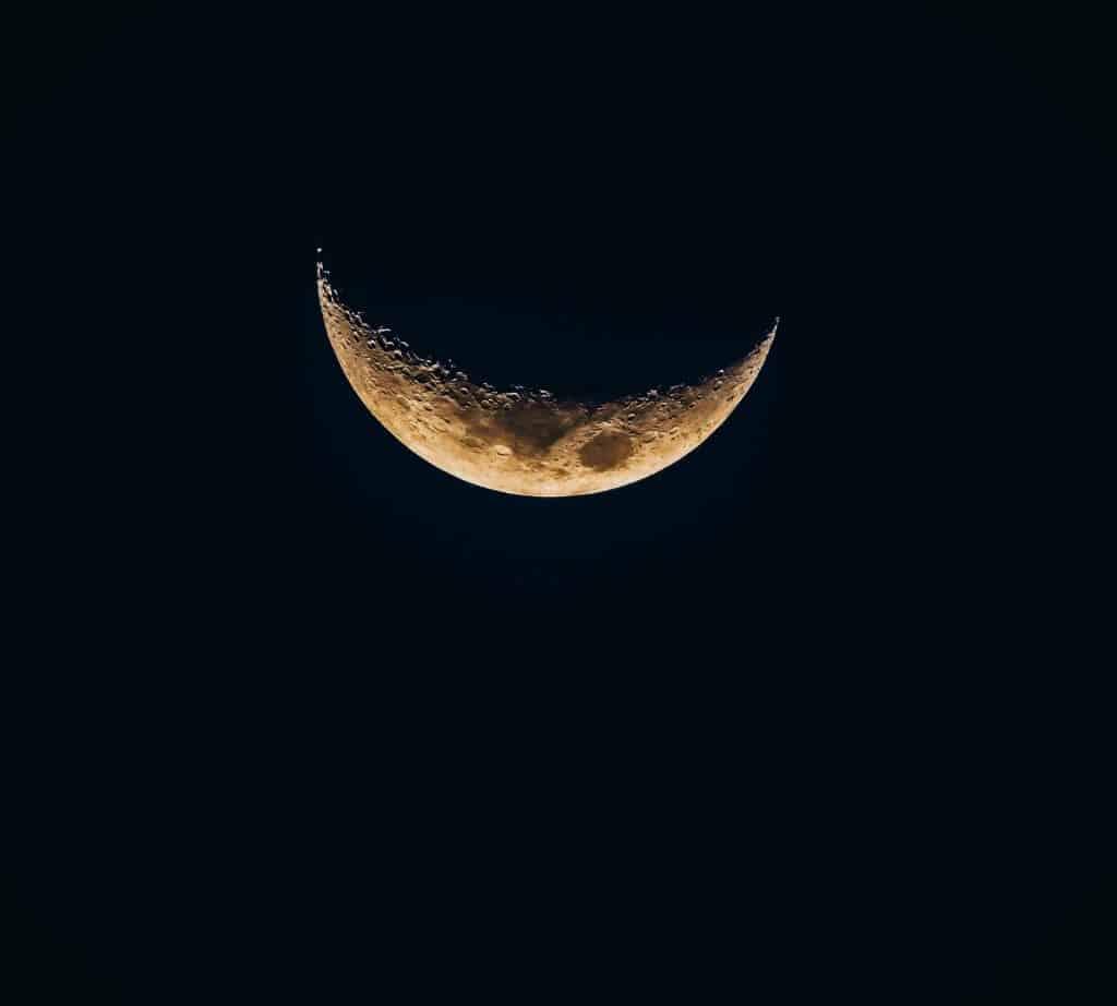 Imagem do céu e ao fundo a lua minguante.