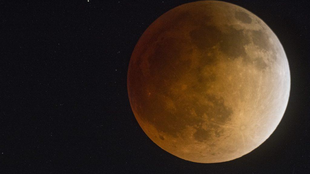 Imagem de uma super lua e ao fundo o céu estrelado.