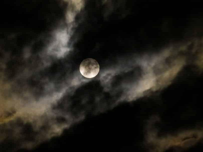 Imagem de um céu encoberto com muitas névoas e ao fundo uma super lua.