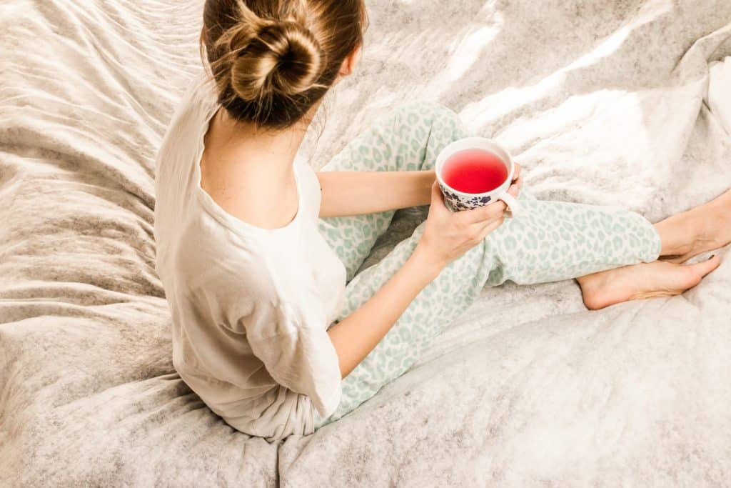 Imagem de uma mulher sentada na cama. Ela usa um pijama confortável e está com um coque no cabelo. Ela segura uma xícara de chá para aliviar os sintomas da TPM.