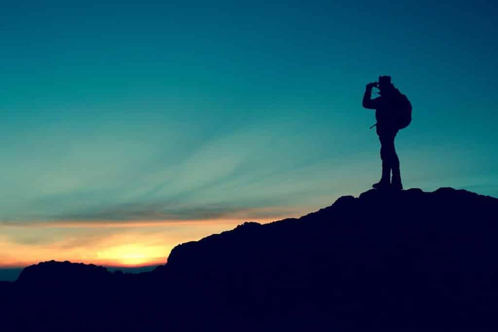 Imagem de um homem no topo de uma montanha. Ele está com uma mochila nas costas e usa um binóculo para observar o lindo pôr do sol no final da imagem.