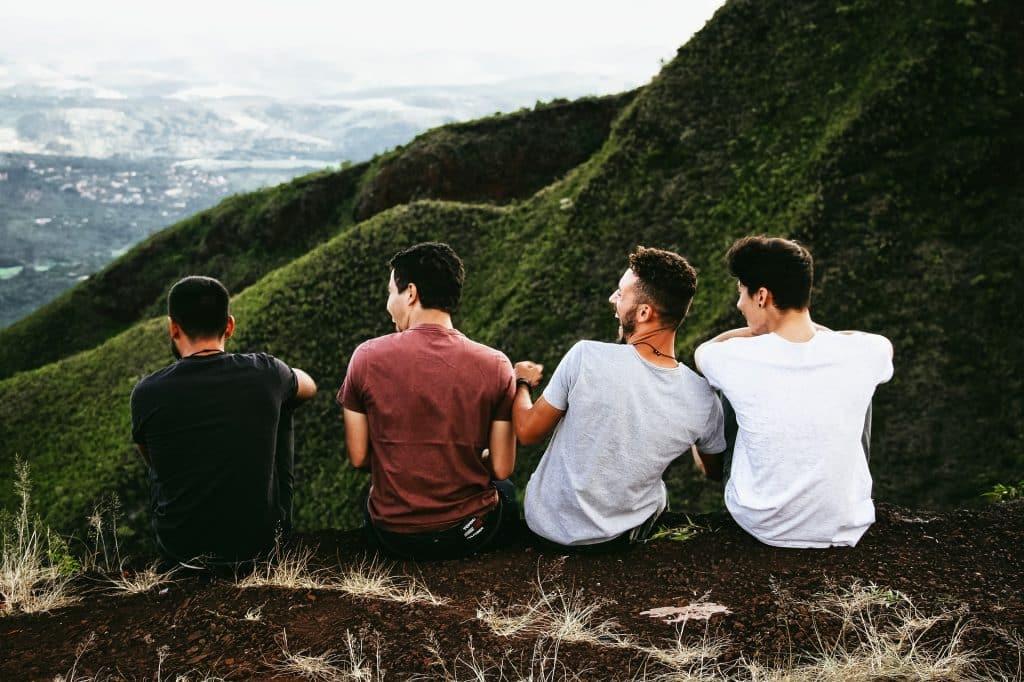 Imagem de quatro rapazes sentados em uma montanha apreciando a natureza. Todos usam camiseta de malha, nas cores preto, vinho, cinza e branco.