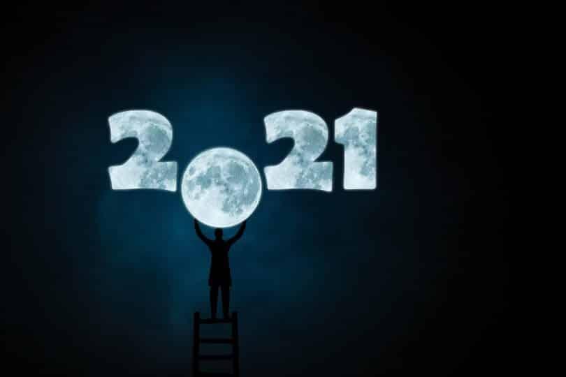 Imagem do ano 2021 desenhando com o fundo da cor da lua. O número zero do ano 2021 está em formato de lua cheia. Um homem está em cima de uma escada e com as mãos segura o número zero em formato de lua.