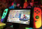 Imagem do controle remoto de um videogame. Na tela do controle imagens de vários ícones de jogos e ao fundo a imagem do Super Mario Bros.