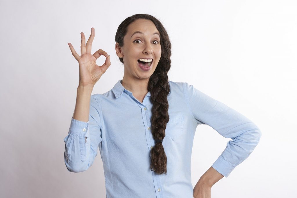 Imagem de uma mulher feliz e dando um ok com uma de suas mãos, confirmando que pessoas que acreditam em signos são mais felizes.