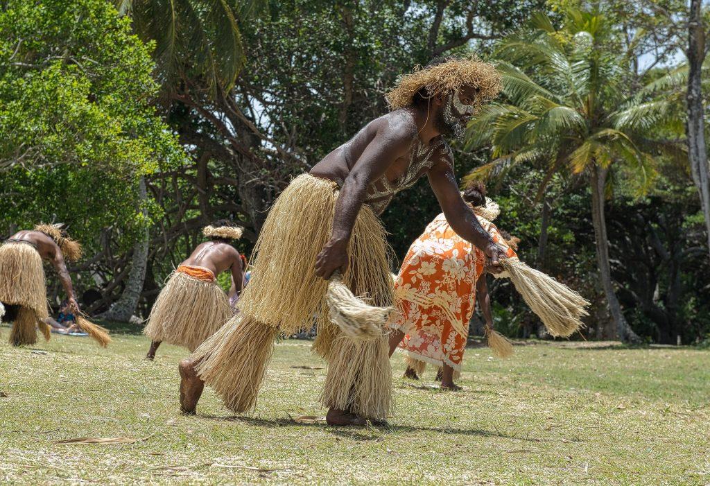 Imagem de homens e mulheres indígenas dançando no terreiro gramado da tribo. Eles usam saias feitas e barbante com um adereço do mesmo material na cabeça. Elas usam vestido longo na cor laranja com flores brancas.