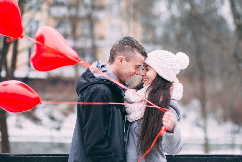 Imagem de um casal um olhando de frente para o outro. Ambos estão agasalhados. Ela usa uma rouca de lã e um cachecol também de lã. Ela segura três balões vermelhos em formato de coração.