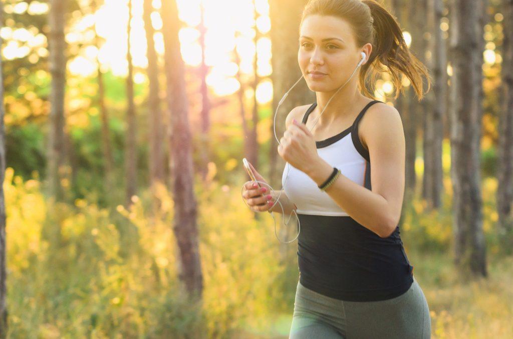 Imagem de uma jovem mulher fazendo exercício físico, ou seja, ela está correndo em um lugar arborizado. Ela usa roupa esportiva e houve música do seu celular com um fone de ouvido.
