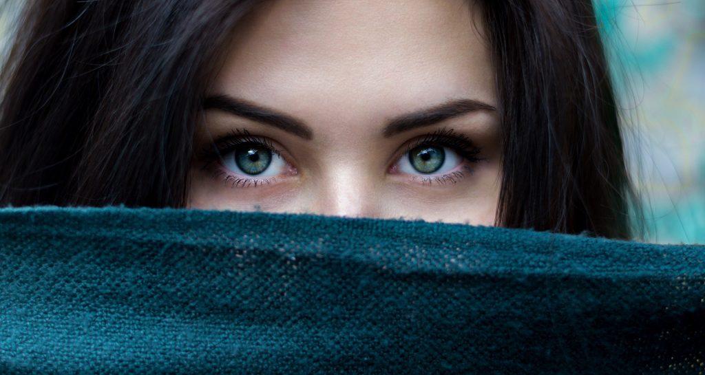 Imagem do rosto de uma mulher com a pele branca e de olhos verdes, com cabelos longos e pretos. Ela segura uma faixa na cor azul tampando o nariz e a boca.