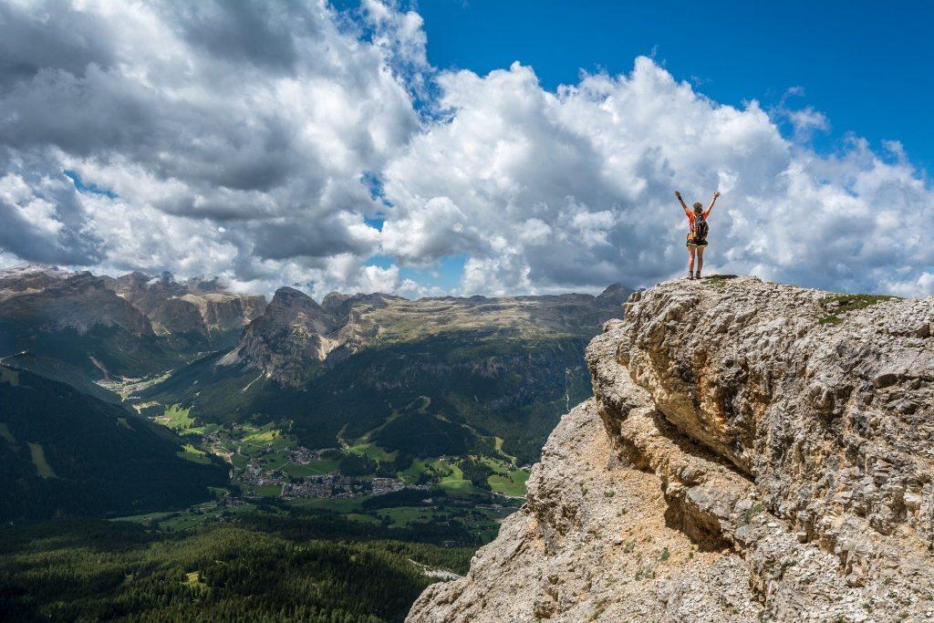 Imagem cujo fundo é representado por um lindo vale com muito verde. Em destaque temos uma mulher de braços abertos, sobre o topo de uma montanha.