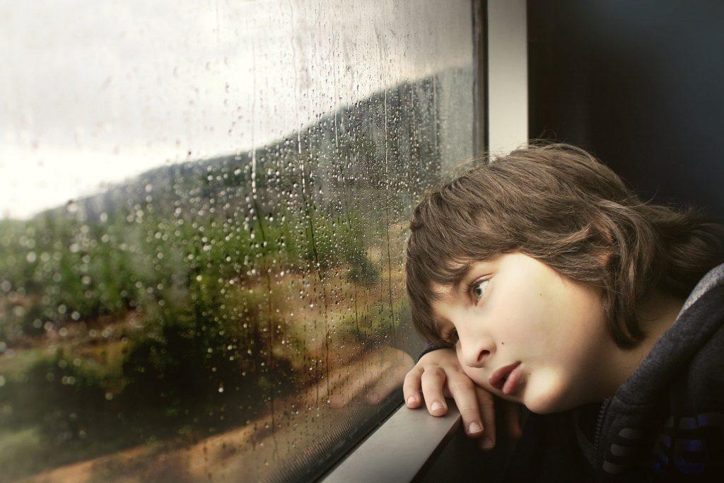 Imagem de um menino triste e debruçado no para peito de uma janela de vidro. A janela está fechada e nela constam pingos de chuva.