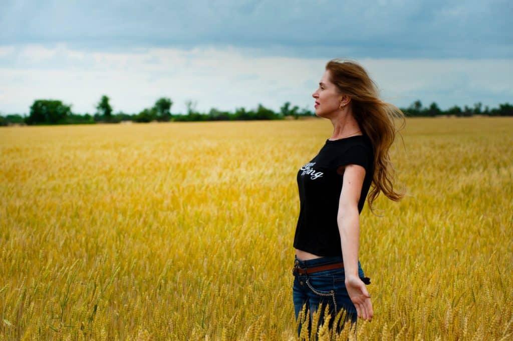 Mulher branca de braços abertos num campo.