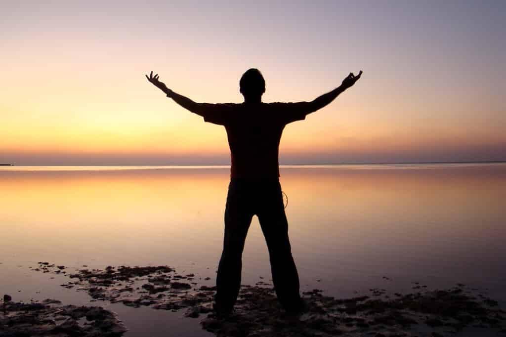 Homem ao horizonte com os braços erguidos.