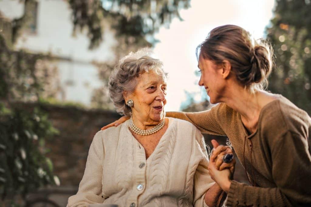 Mulher jovem abraçando e dando a mão para uma mulher idosa.