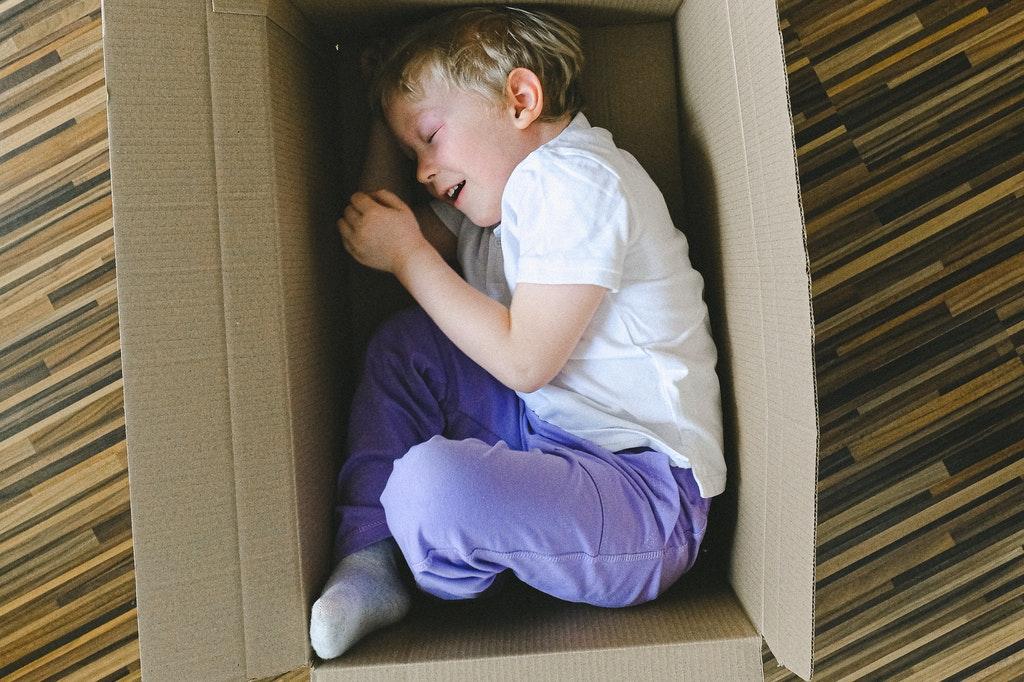 Criança deitada dentro de uma caixa de papelão.