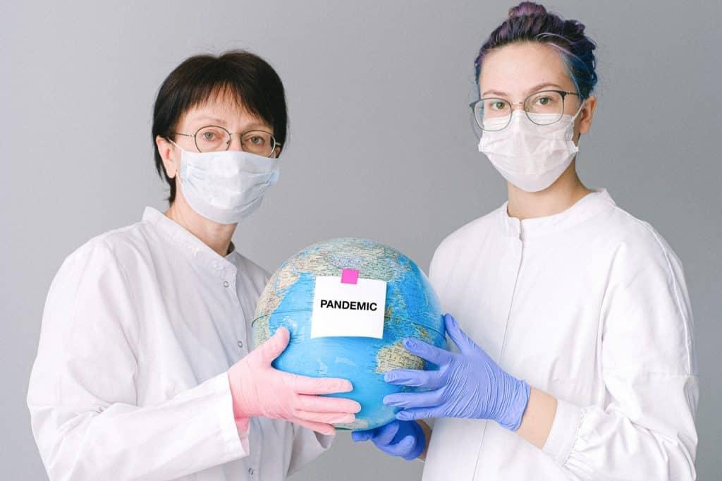 """Duas mulheres de máscara e roupa branca segurando o globo com uma plaquinha de """"pandemia"""""""