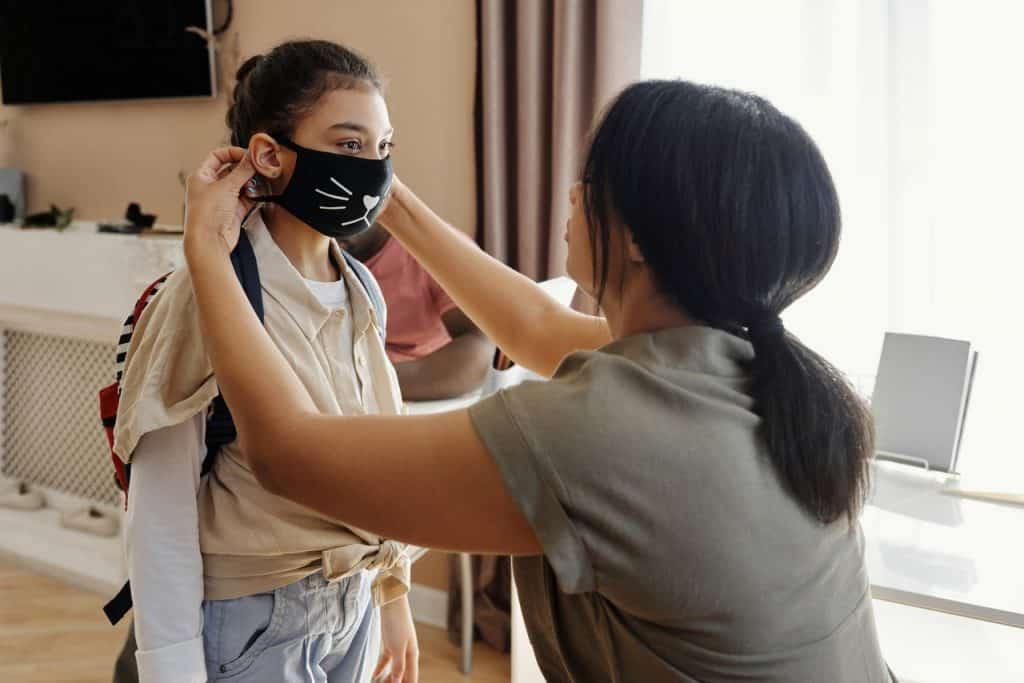 Uma mãe colocando a máscara na filha.