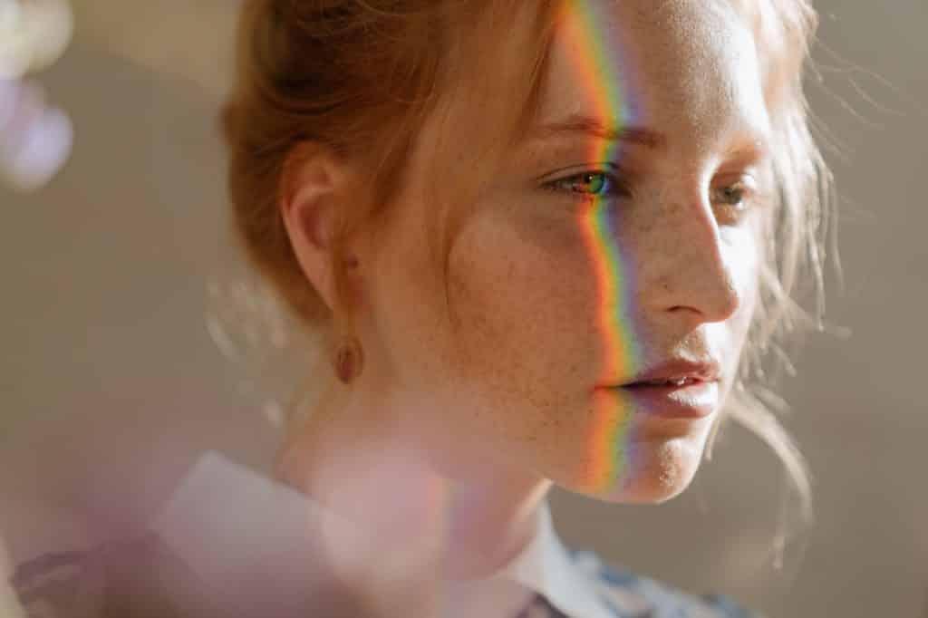 Mulher branca com reflexo de arco-íris no rosto.