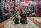 Duas mulheres ajoelhadas no chão jogando confete colorido para o alto