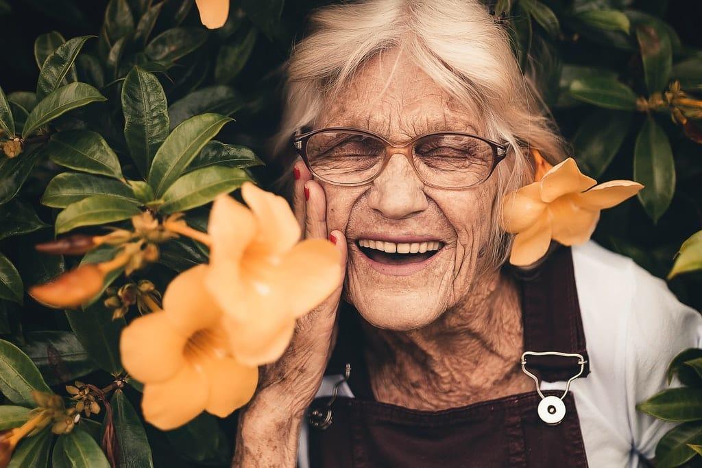 Idosa sorri entre flores amarelas.