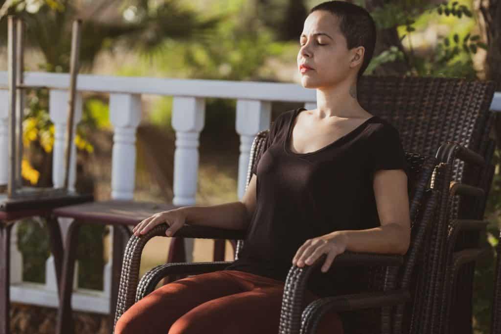 Mulher sentada em uma cadeira ao ar livre com os olhos fechados meditando.