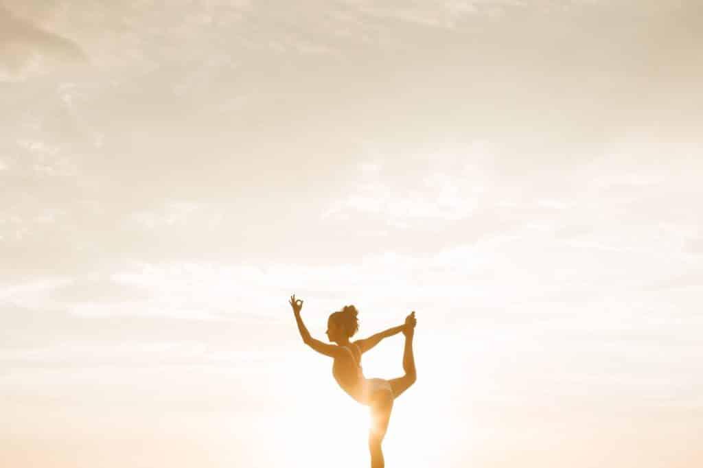 Mulher meditando de pé com o pôr do sol ao fundo.