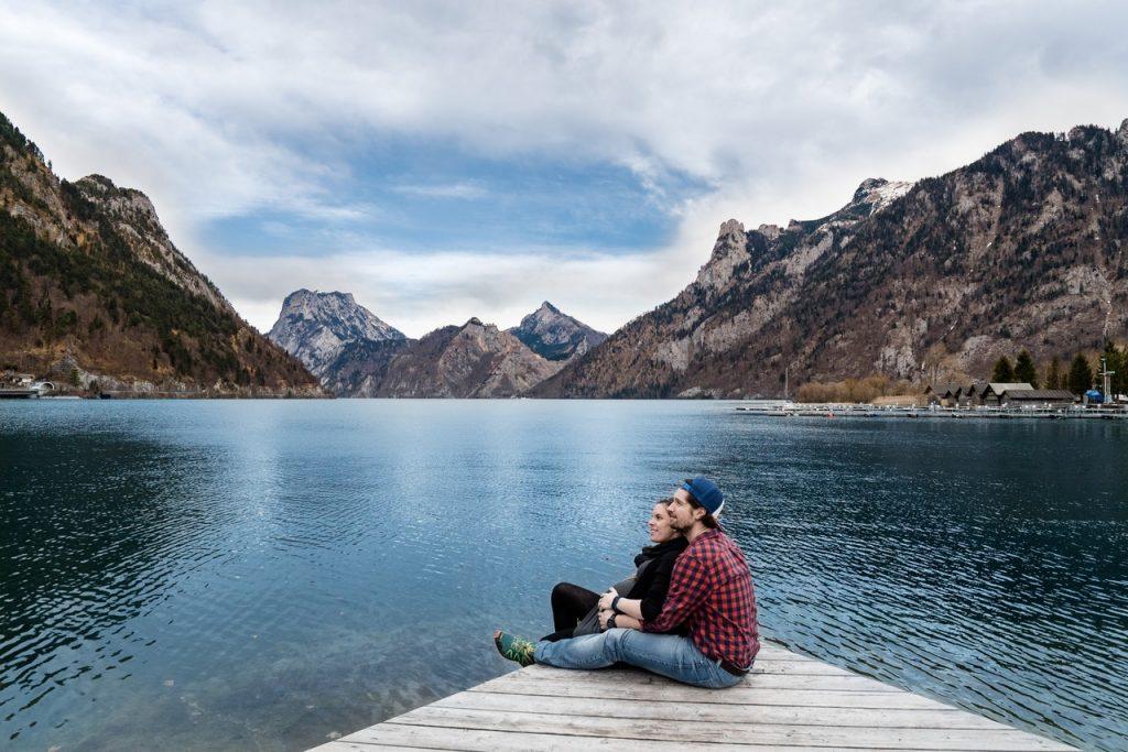 Casal sentados no chão abraçados olhando o mar com montanhas em volta.