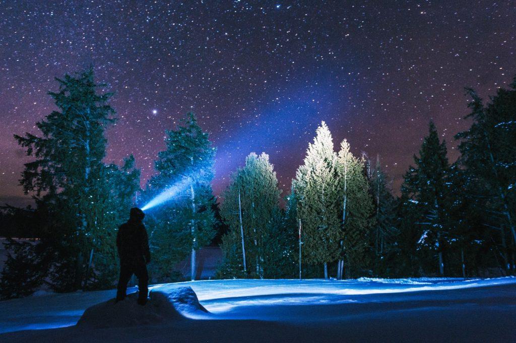 Silhueta de um homem segurando uma lanterna apontada para o alto. Está uma noite estrelada em montanhas cheias de neve.