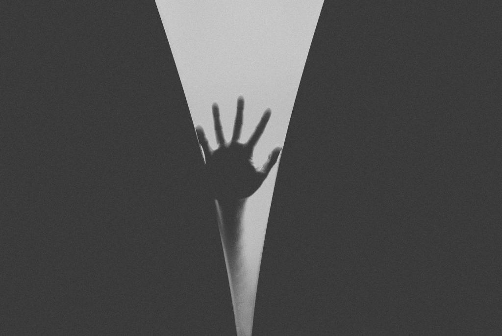 Recorte de uma mão apoiando em um vidro.
