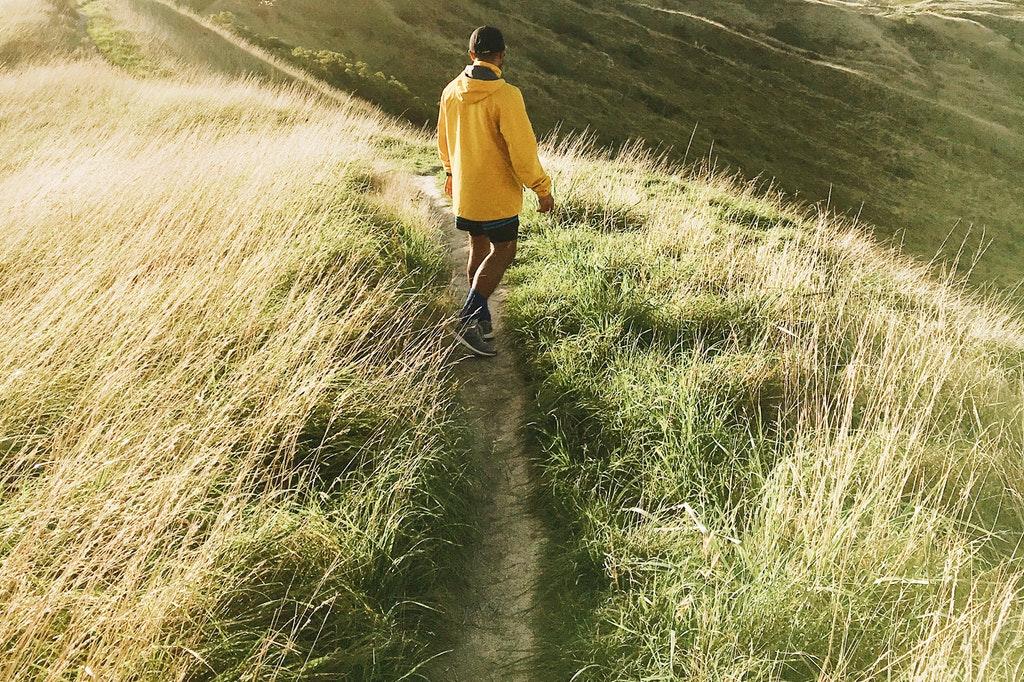 Homem andando em meio a grama.