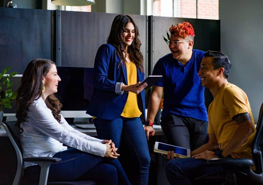 Grupo de quatro jovens em círculo conversando e rindo.