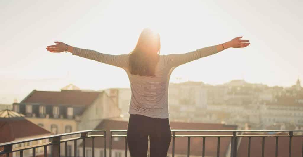 Mulher com os braços abertos de costas admirando a paisagem.