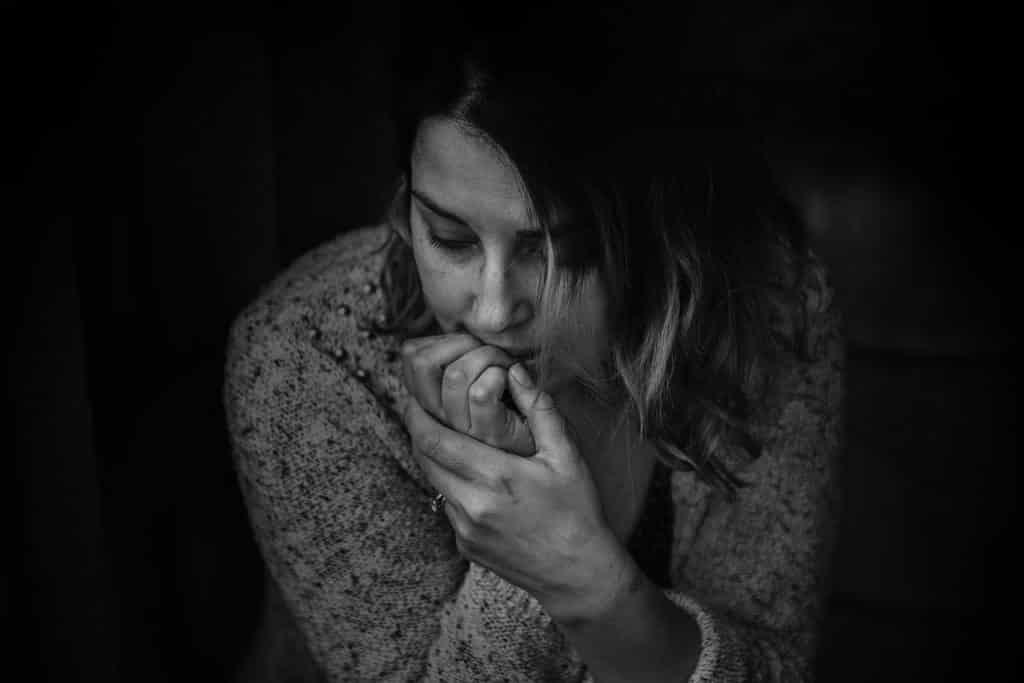 Imagem em preto e branco de uma mulher em conflito.