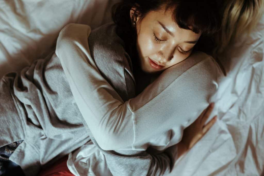 Duas mulheres deitadas na cama abraçadas.