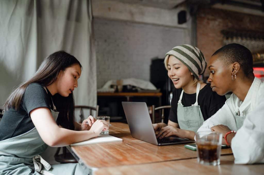 Três jovens sentadas na mesa de madeira conversando.