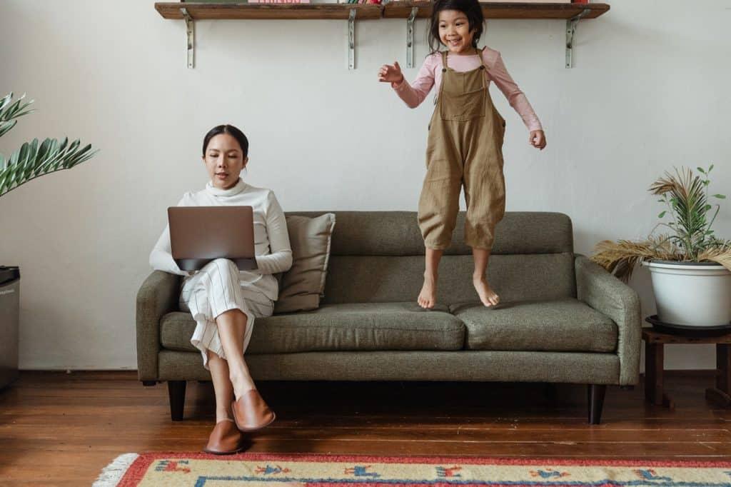 Mulher sentada no sofá mexendo no notebook, enquanto uma criança está pulando no sofá.
