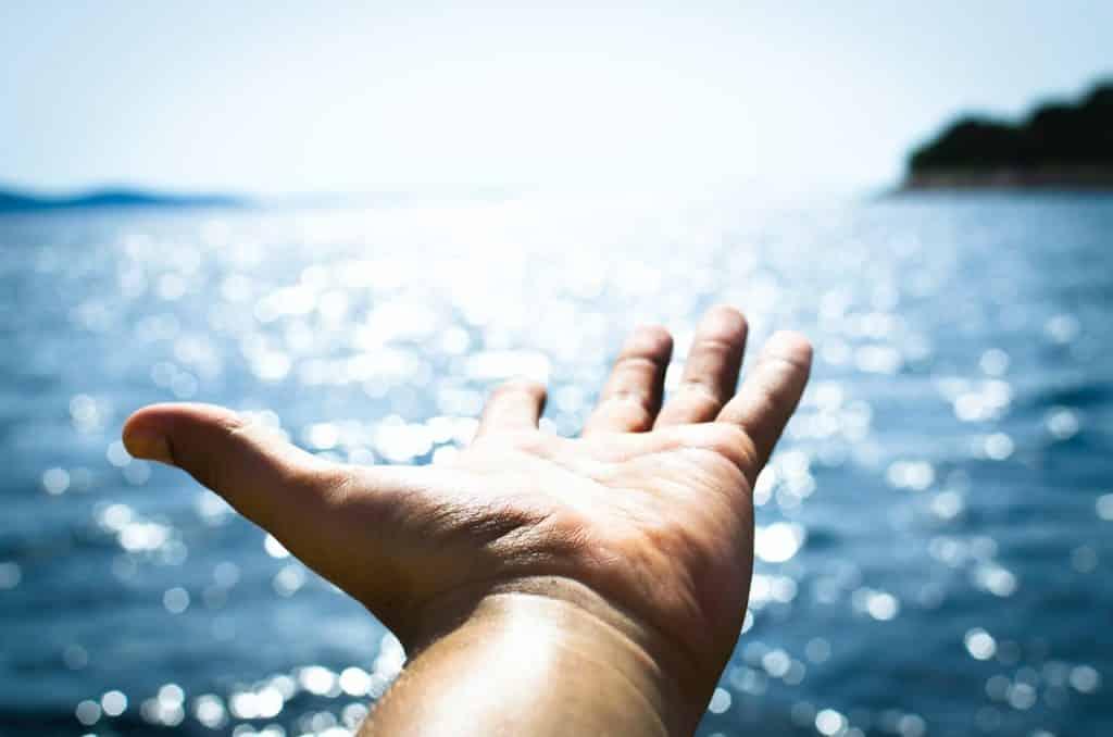 Mão estendida sobre paisagem de oceano.