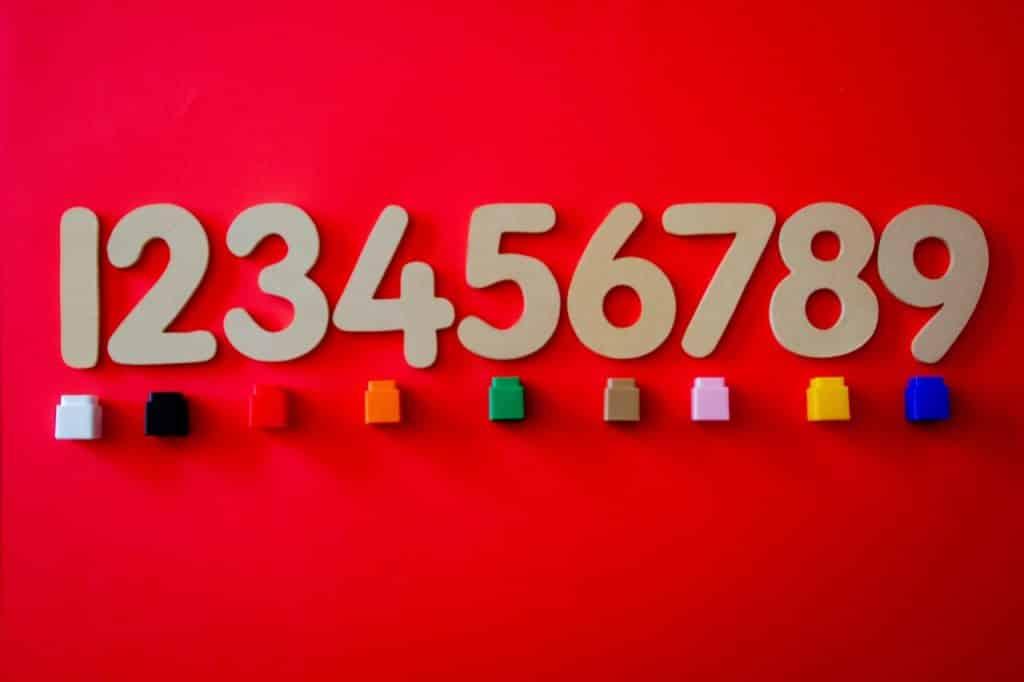 Números de um a nove colocados sobre o fundo vermelho com pedrinhas coloridas embaixo.