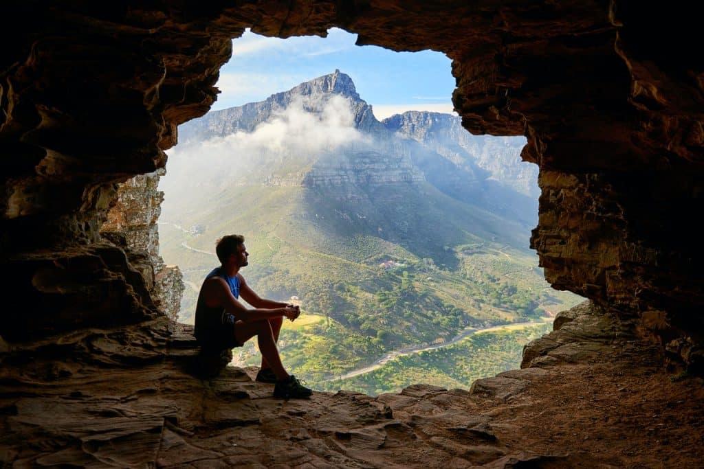 Um homem sentado em uma caverna observando a natureza.