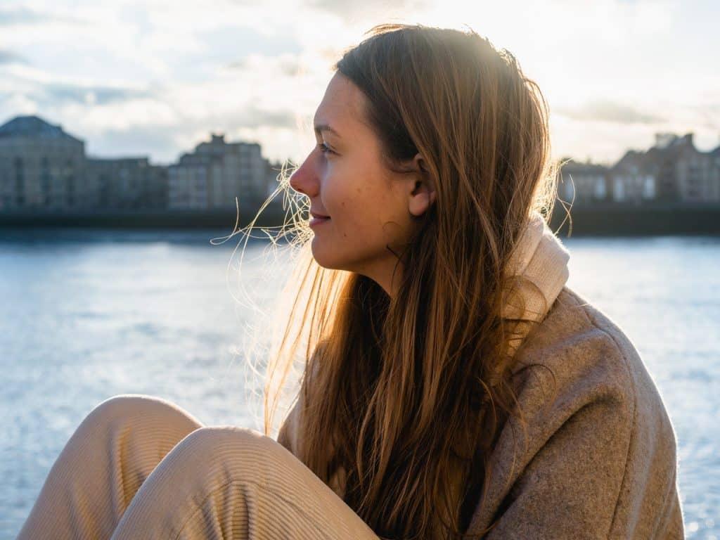 Mulher sentada perto de um lago. Ela está sorrindo e olhando para o lado.