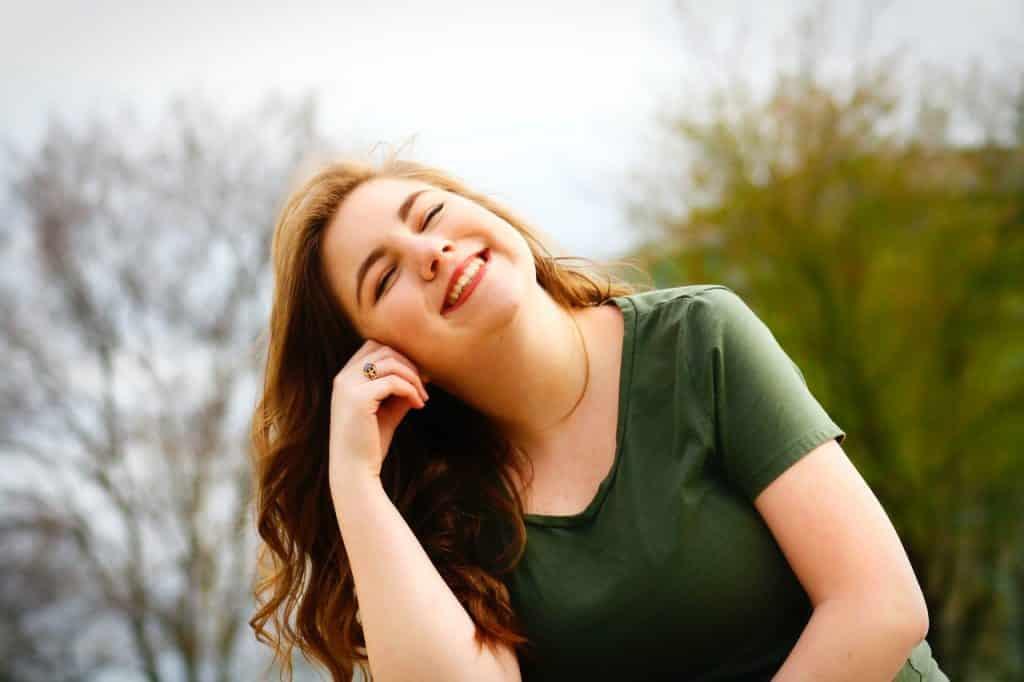 Mulher com blusa verde sentada no chão com os olhos fechados e uma das mãos apoiada na cabeça enquanto sorri.