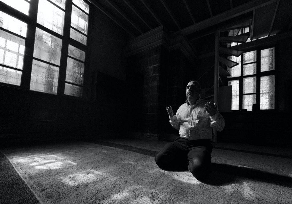 Imagem preta e branco de um homem ajoelhado no chão rezando.