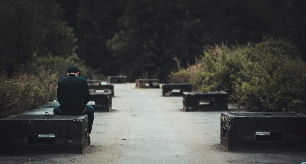 Homem sentado em um dos vários banquinhos da imagem com a cabeça baixa.