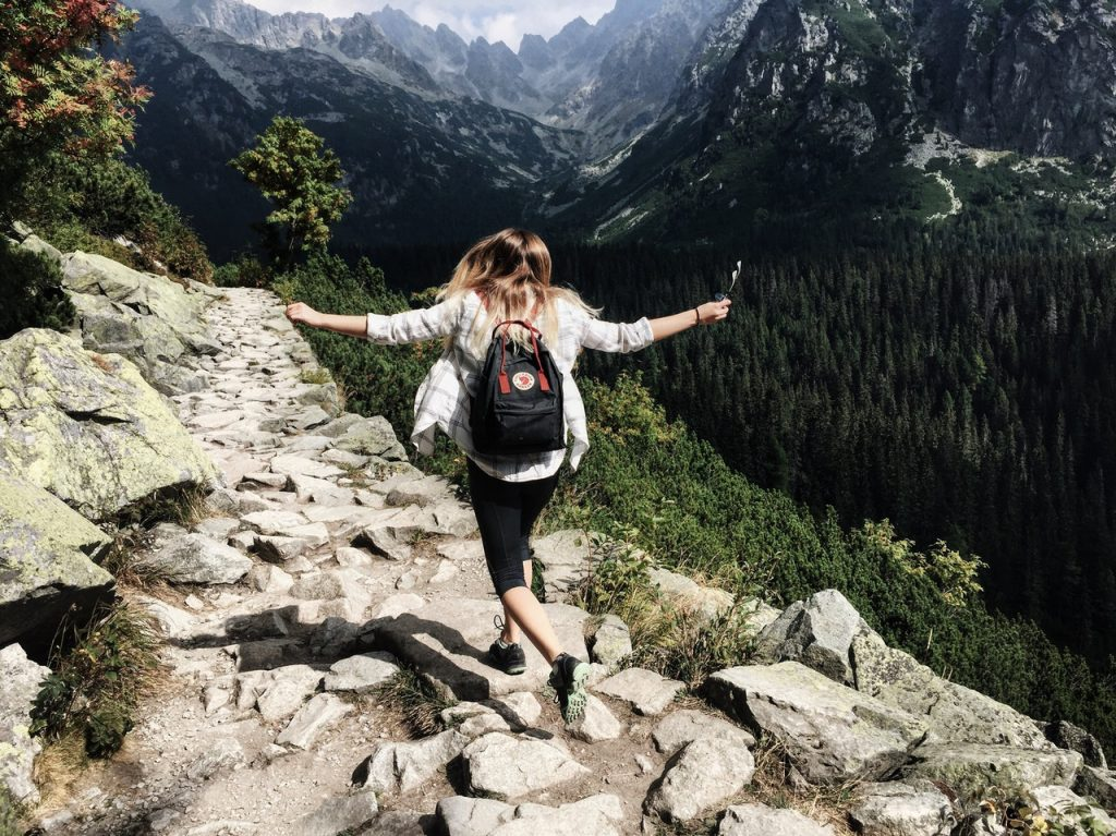 Mulher com os braços erguidos caminha sobre pedras.