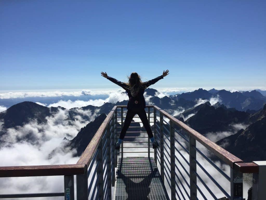 Menina de roupa preta admirando montanhas, pendurada nas escadas com os braços abertos.