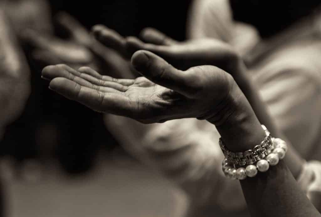 Imagem preta e branco de uma mão rezando.