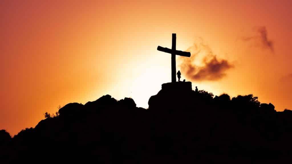 Uma cruz no alto de uma montanha com o pôr do sol ao fundo.