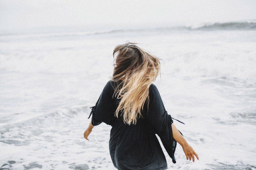 Mulher entrando em mar.