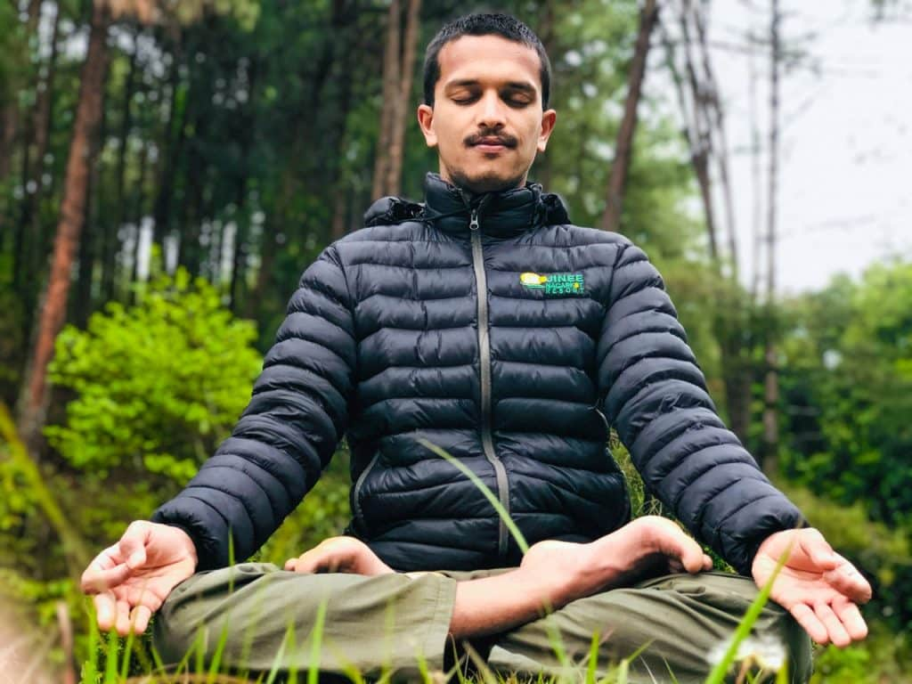 Homem de jaqueta azul e calças-verde meditando no meio da natureza.