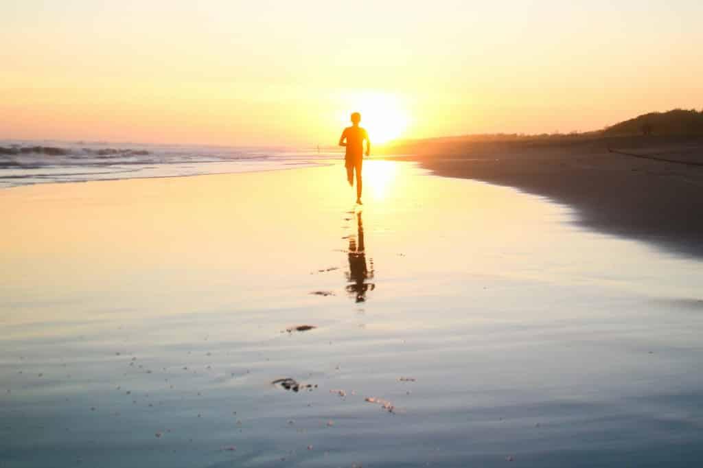 Silhueta de homem correndo refletida na água.